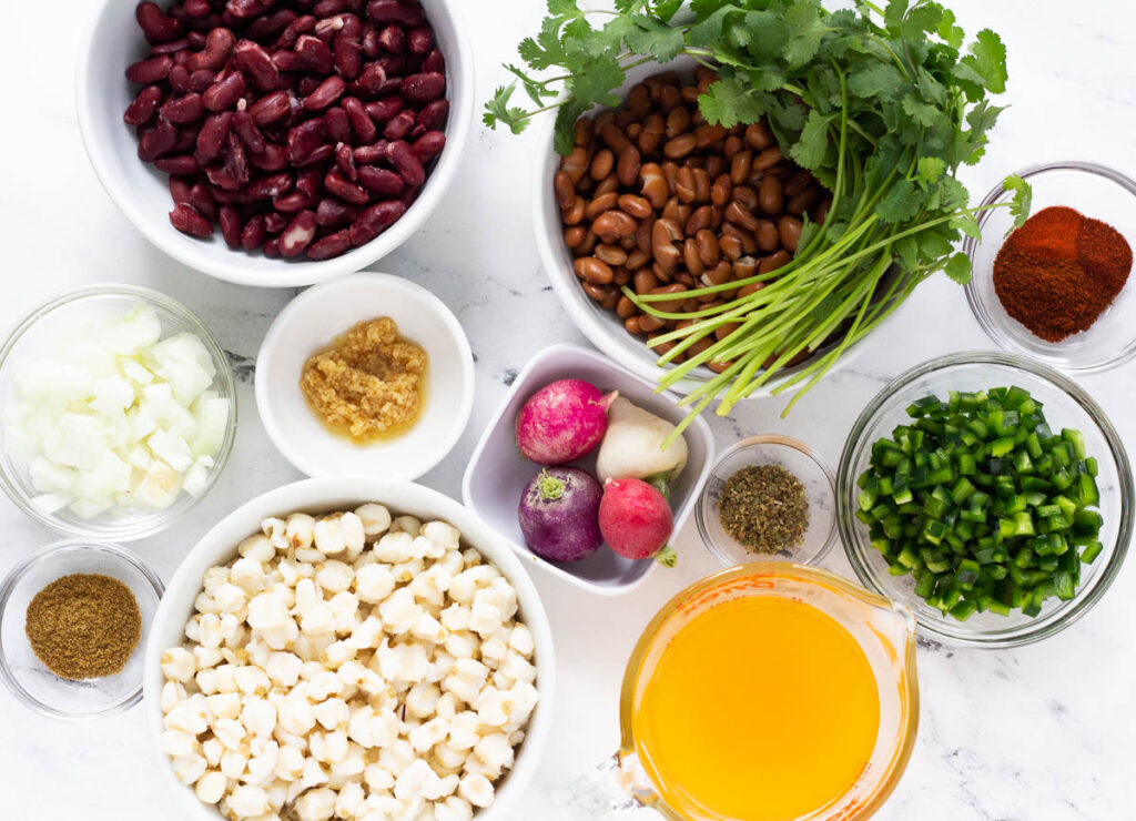 vegan pozole ingredients: kidney beans, pinto beans, clialntro, chili pepper, diced poblano peppers, vegetable broth, oregano, radishes, hominy, garlic, onion, and cumin