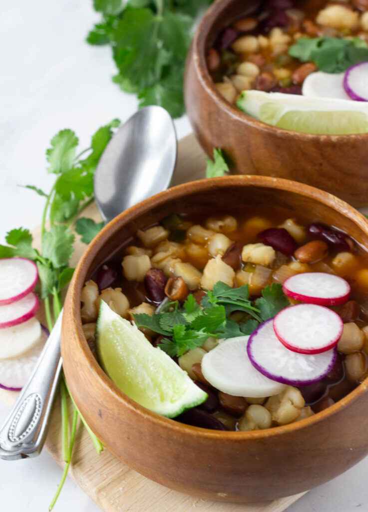 vegan pozole in wood bowl topped with radishes, cilantro, and lime wedge