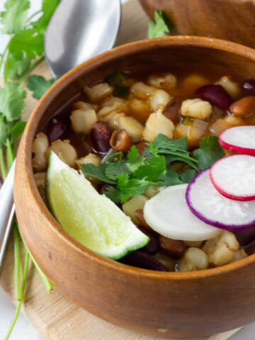 vegan pozole in wood bowl topped with radish slices, cilantro and lime wedge