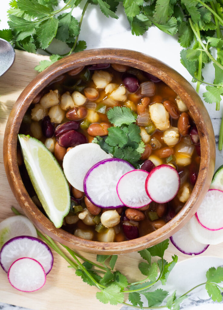 vegan pozole in wood bowl topped with radish slices, cilantro, and lime wedge