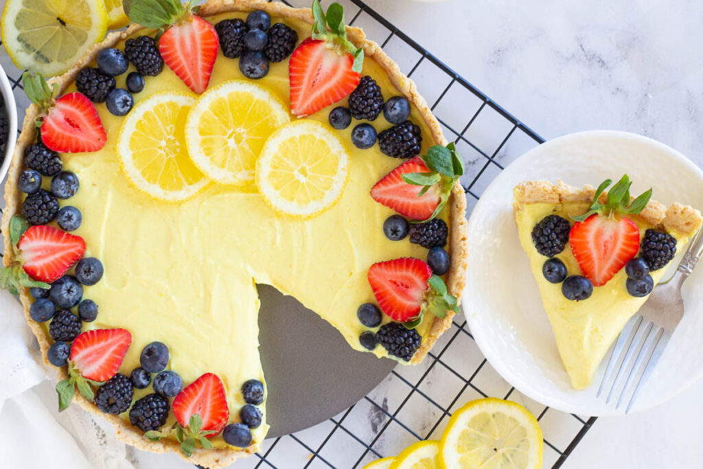 vegan lemon tart with slice cut out on plate beside it, topped with fresh berries and lemon slices
