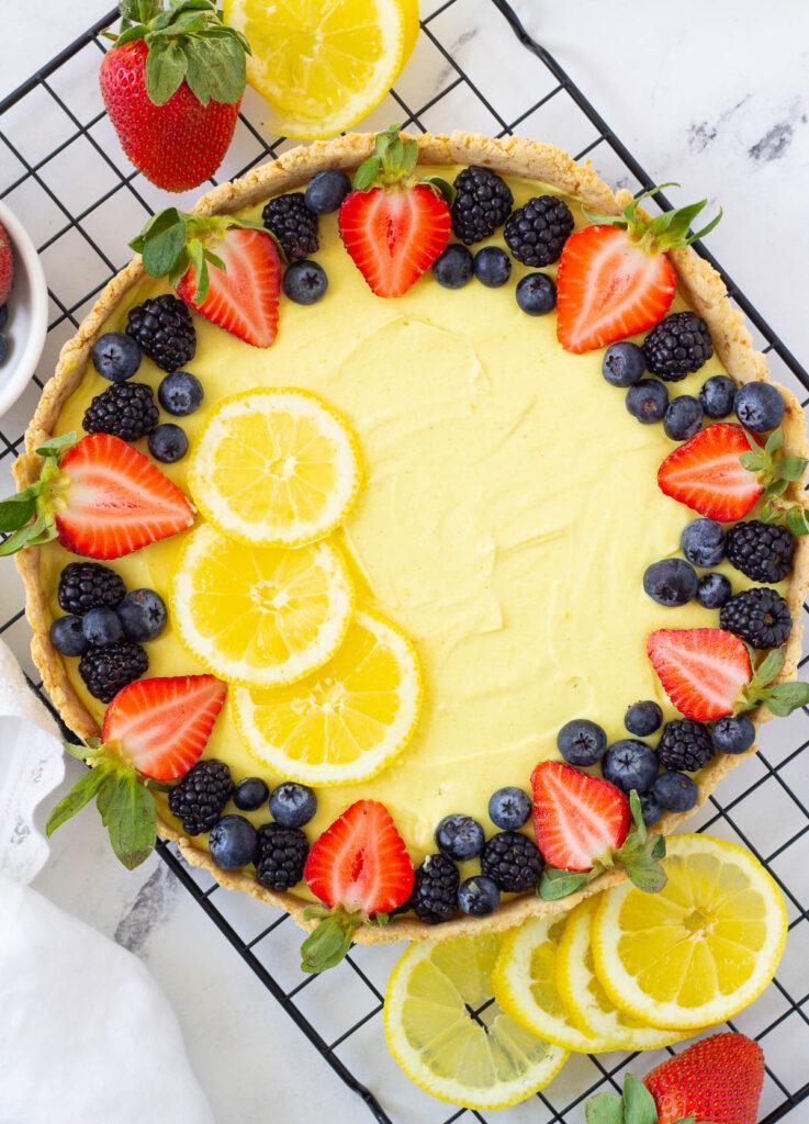 vegan lemon tart with fresh berries and lemon slices
