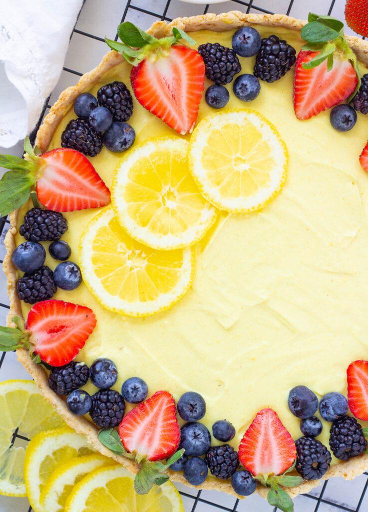 Vegan tart topped with lemon slices, and fresh berries