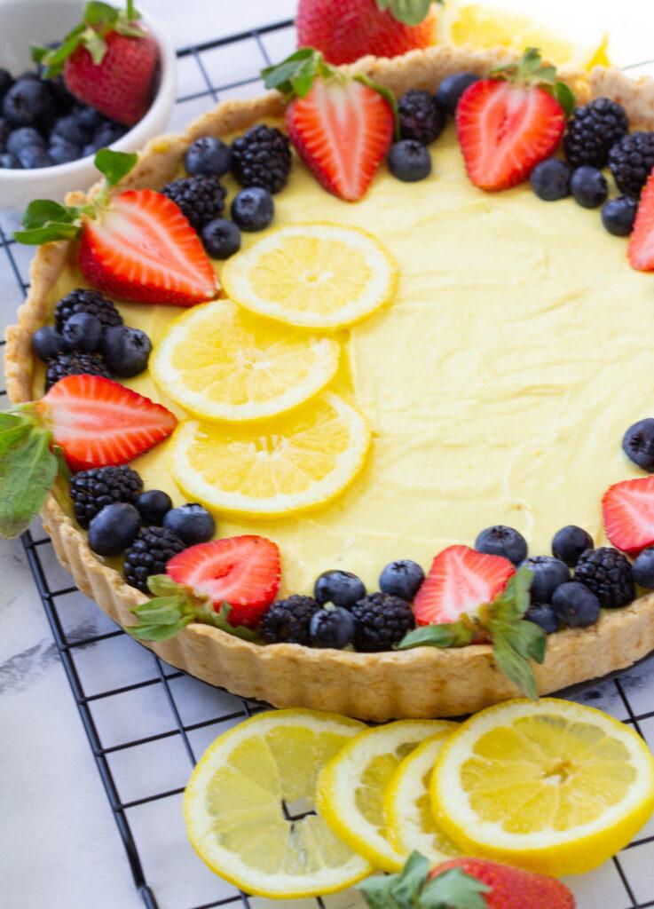 vegan tart topped with lemon slices, strawberries, blackberries, and blueberries