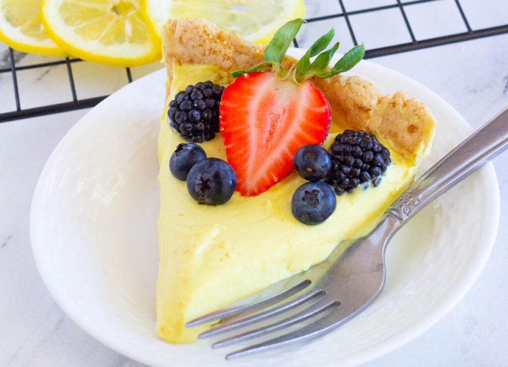 slice of vegan lemon tart topped with strawberry, blackberries, and blueberries