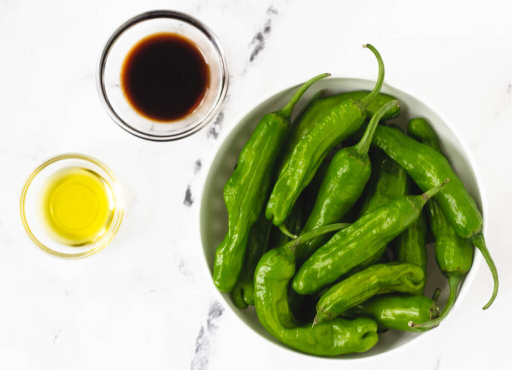 soy sauce, olive oil, and shishito peppers in bowls