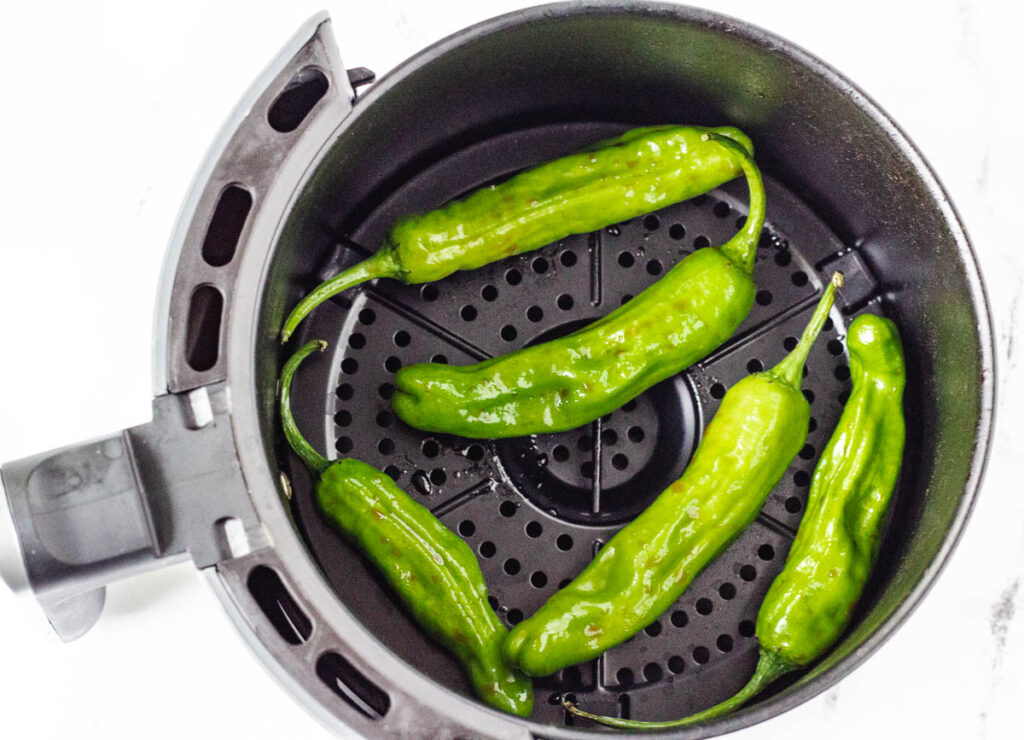 raw shishito peppers in air fryer basket