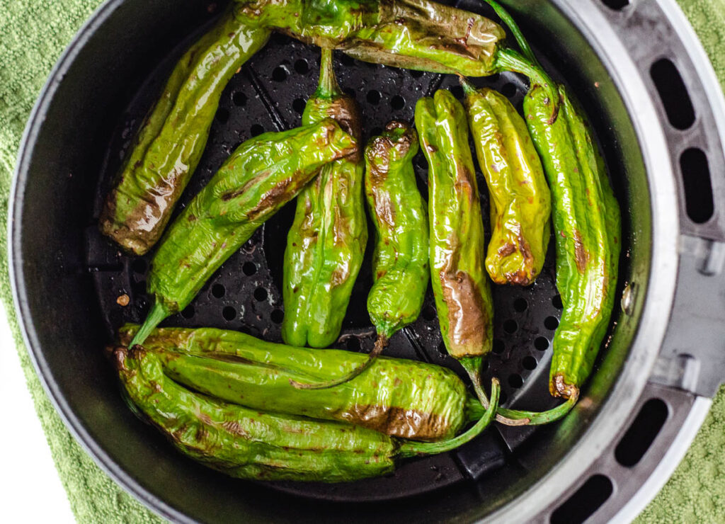 blistered shishito peppers in air fryer basket