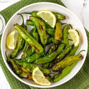 air fryer shishito peppers in white bowl with lemon wedges