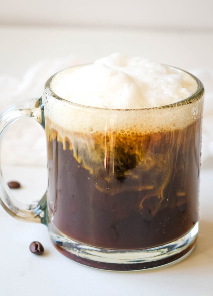 almond milk in glass mug topped with lots of foam