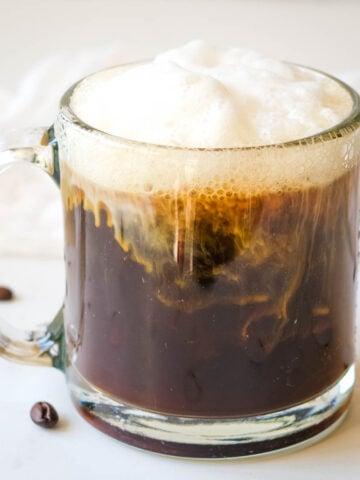 almond milk latte in glass cup with lots of foam