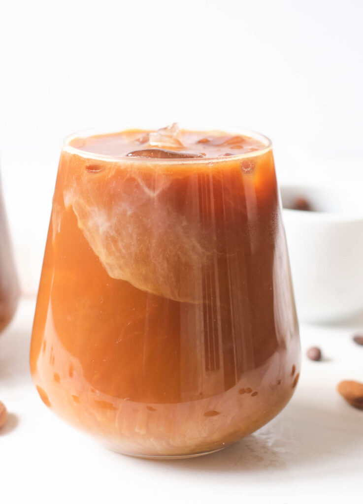 iced almond milk latte in glass with ice
