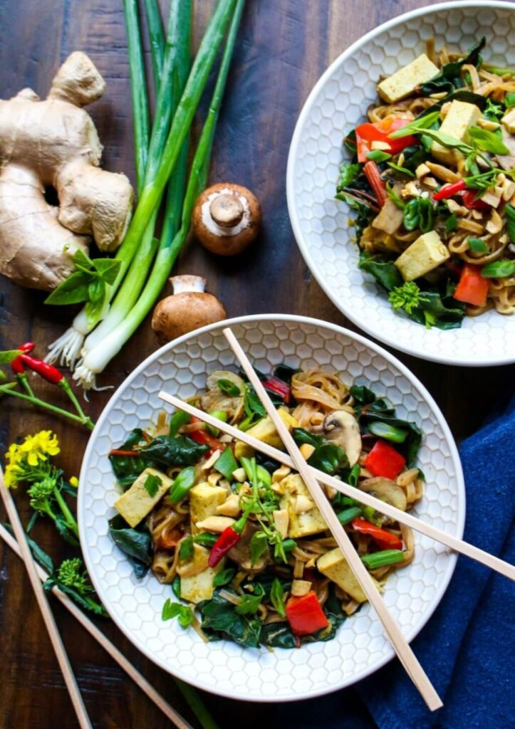 Thai tofu veggie noodle bowl surrounded by fresh vegetables with chop sticks lying on top of the bowl