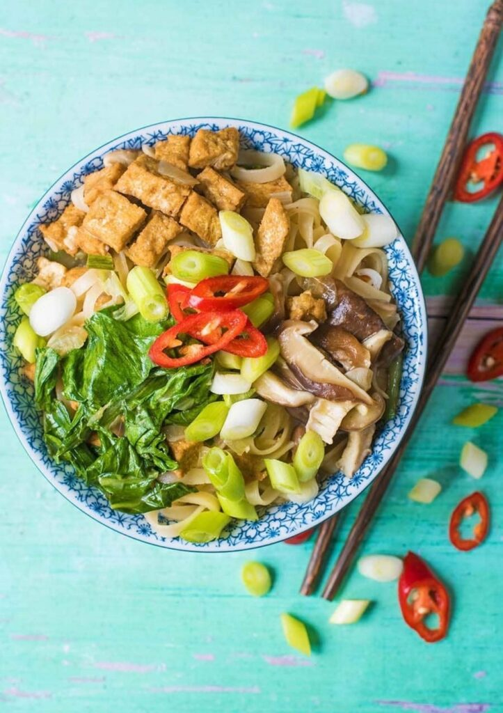 large noodle bowl with mushrooms, greens, tofu, and scallions