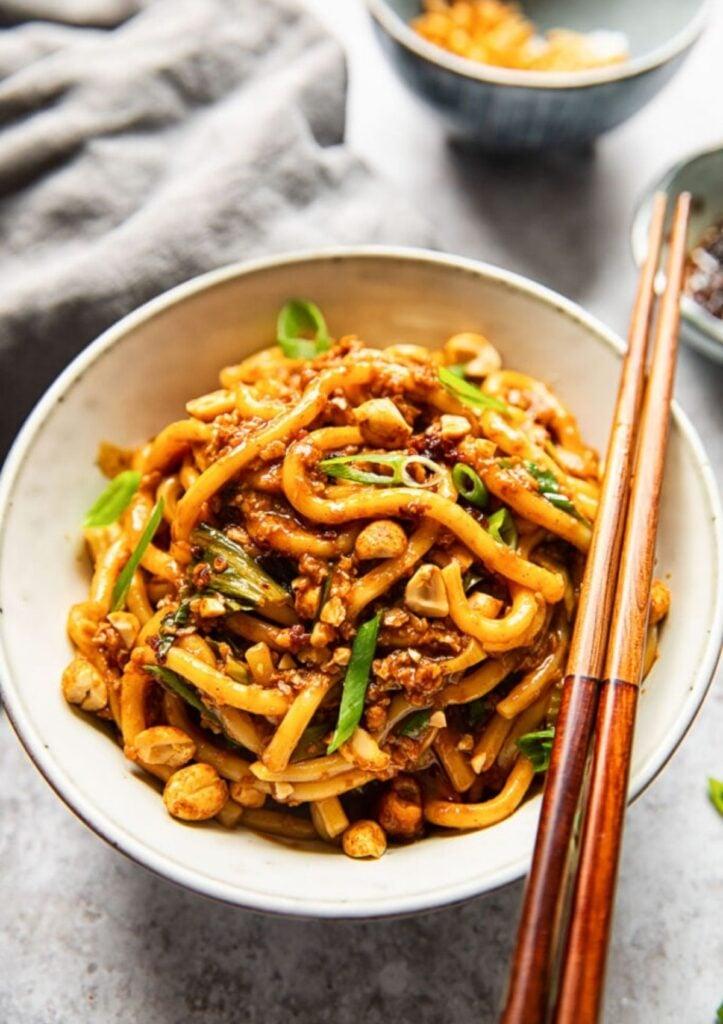 vegan dan dan noodles in ceramic bowl with chop sticks