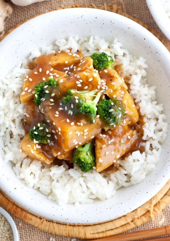 Orange flavored tofu and broccoli served over white rice and sprinkled with sesame seeds