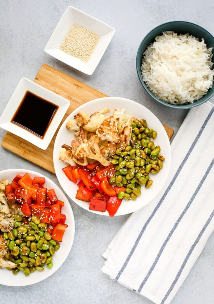 seasoned edamame, cauliflower, and red pepper served on a white plate with a side of rice and soy sauce