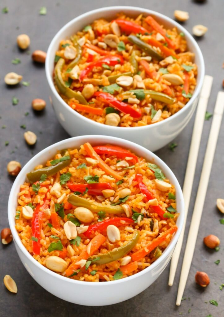 Thai Coconut Curry Rice in two bowls topped with peanuts and peppers