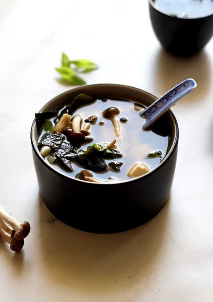 Miso Soup in small black bowl with mushrooms and greens