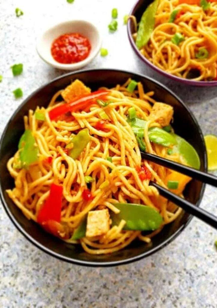 garlic noodles in black bowl with chop sticks