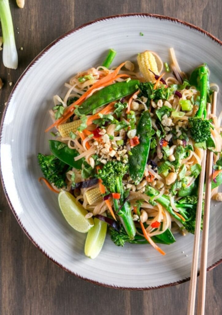easy pad thai on ceramic plate with snow peas, broccoli, and chopped nuts