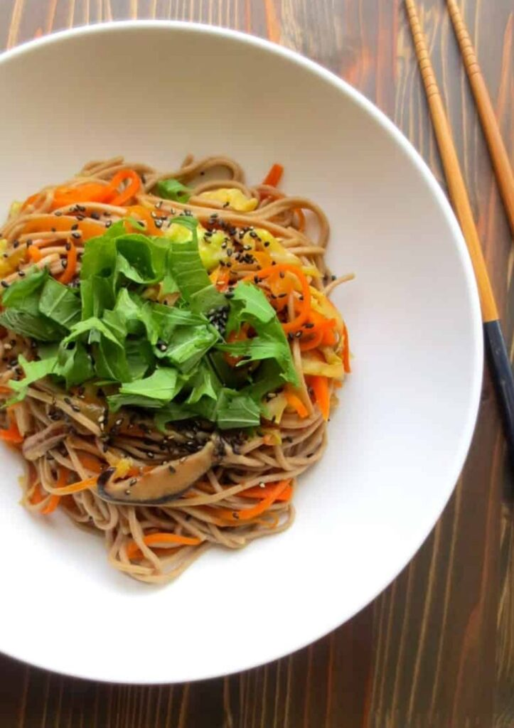 soba noodles in wide white bowl topped with chopped greens