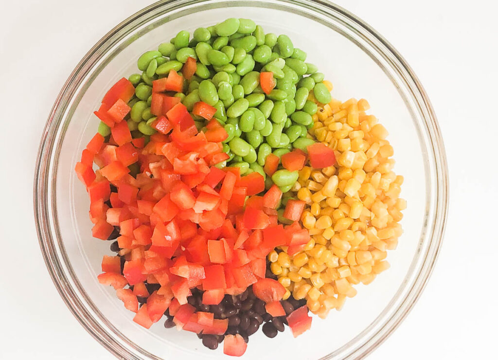 edamame, red pepper, corn, and black beans in glass bowl