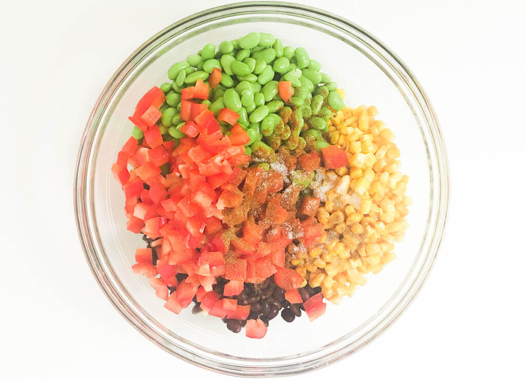 red peppers, corn, edamame, and black beans topped with spices in glass bowl