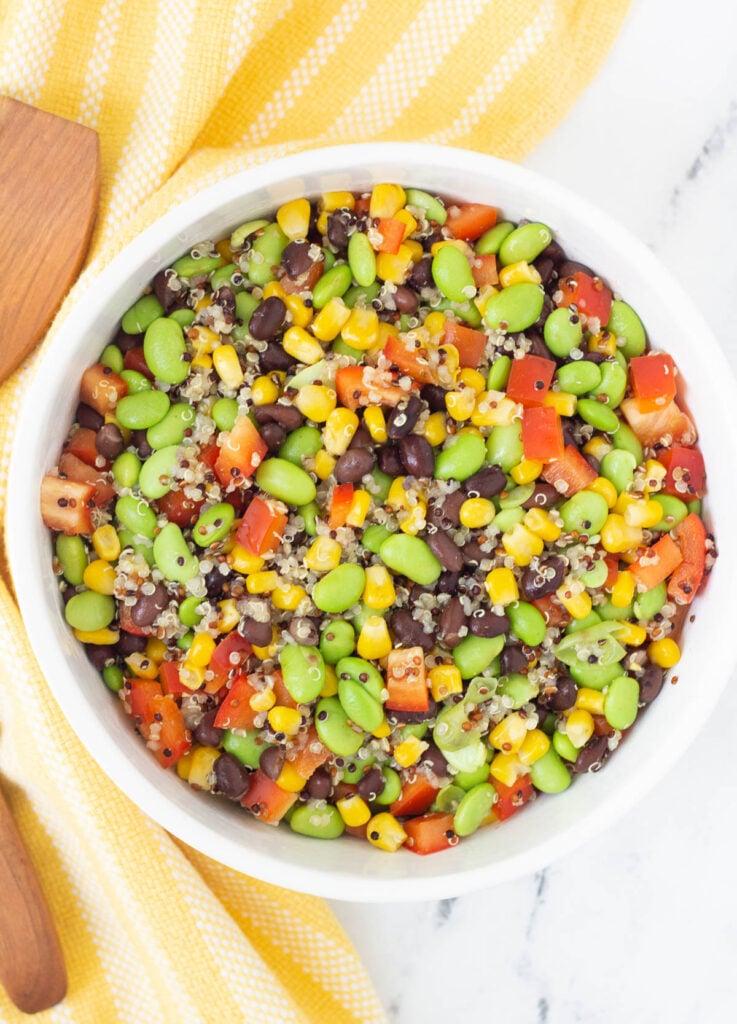 black bean edamame salad in white serving bowl