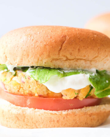 vegan chickpea patty burger on whole wheat bun with lettuce, tomato, and dill sauce