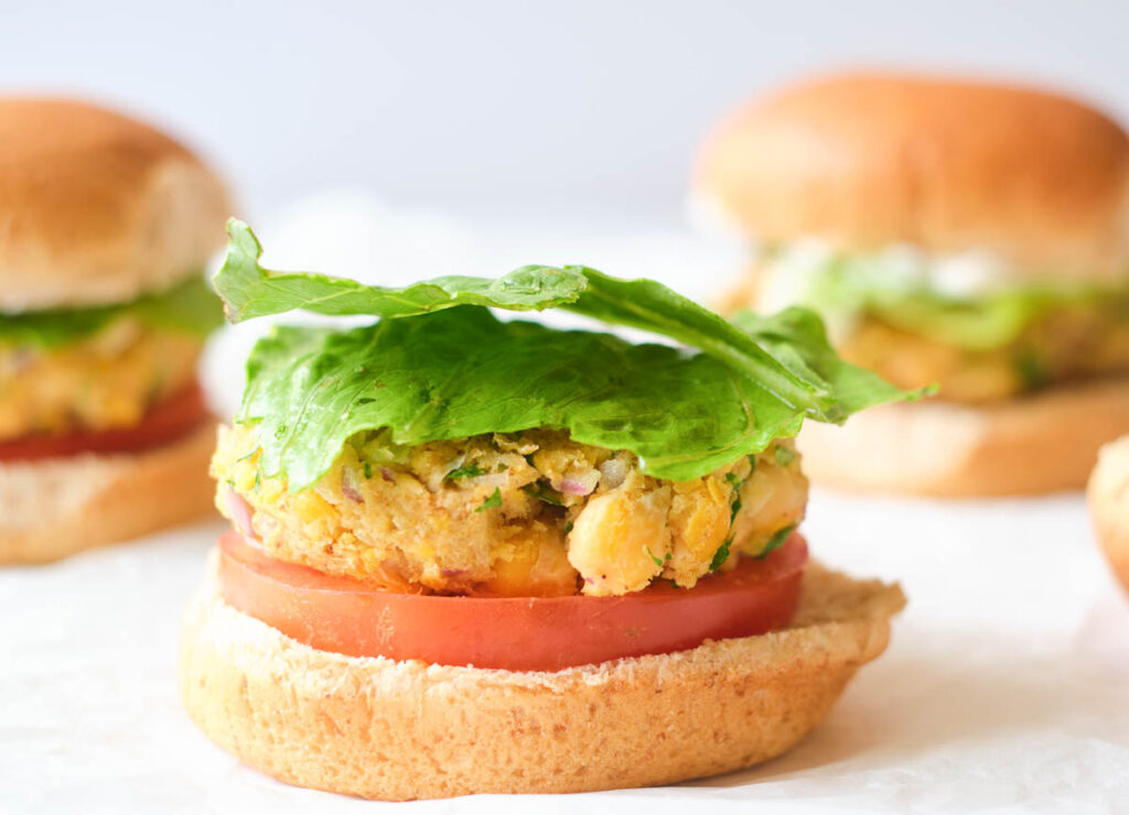 bottom of whole wheat bun topped with tomato slice, chickpea burger, and two pieces of lettuce
