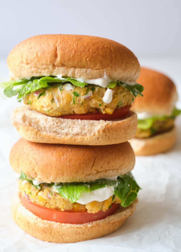 stack of vegan chickpea patties between whole wheat buns with lettuce, tomato, and dill sauce