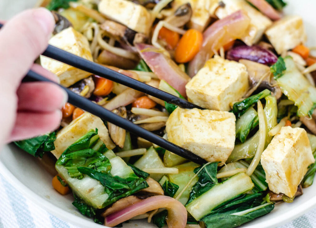 hand picking up a piece of tofu with chop sticks in bowl of stir-fried vegetables