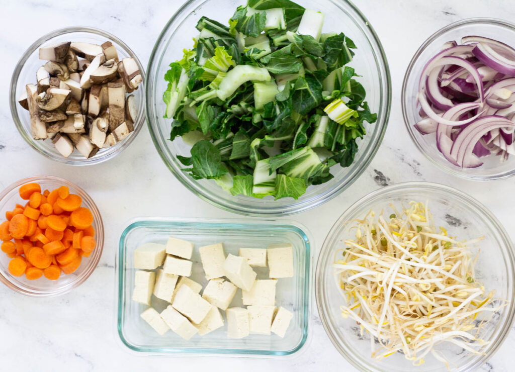 chopped mushrooms, bok choy, sliced onions, mung bean sprouts, cubed tofu, and diced carrots in small bowls
