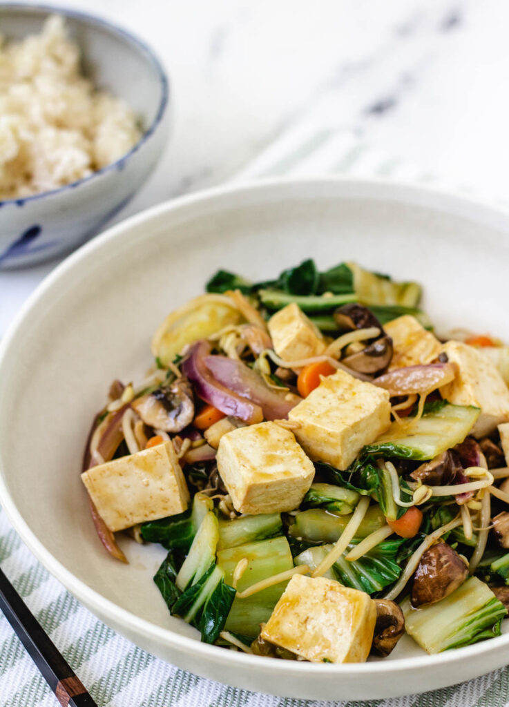 vegan chop suey with stir-fried vegetables and cubed tofu in wide bowl, served with side of brown rice