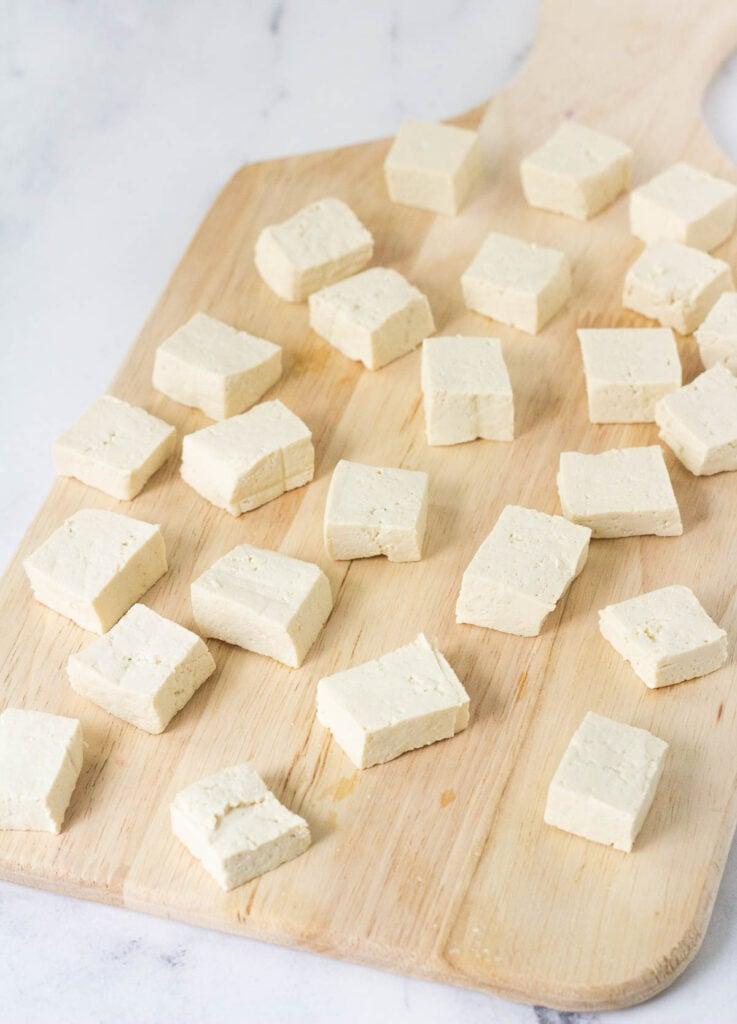 tofu block and tofu pieces on wood cutting board