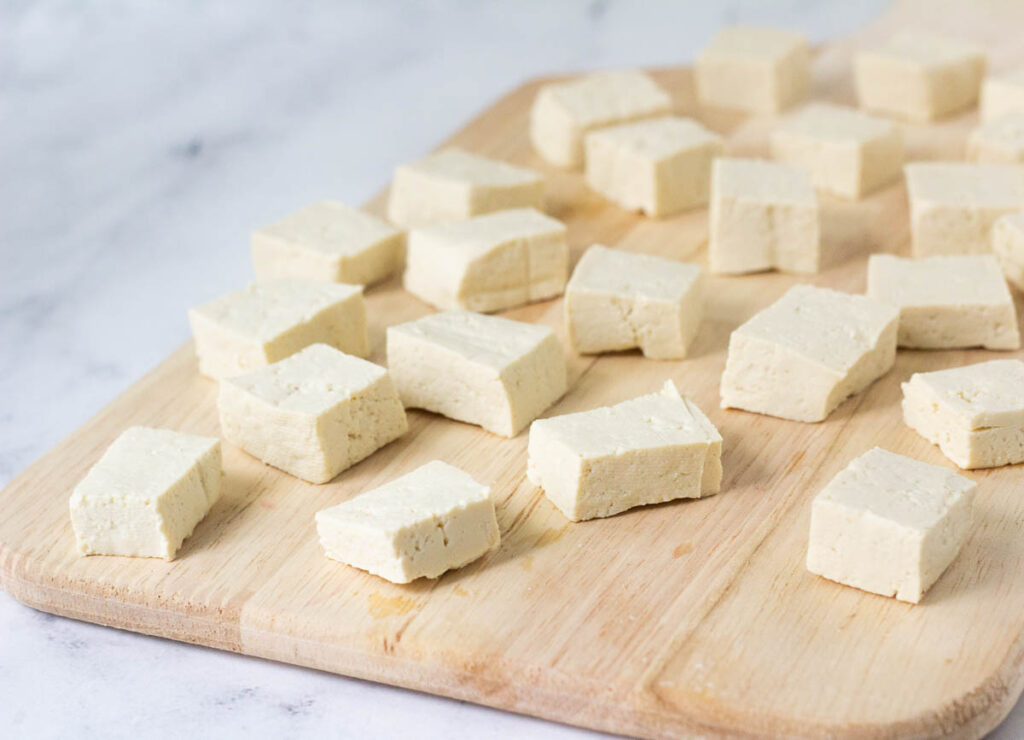 tofu block and chopped tofu cubes on wood cutting board