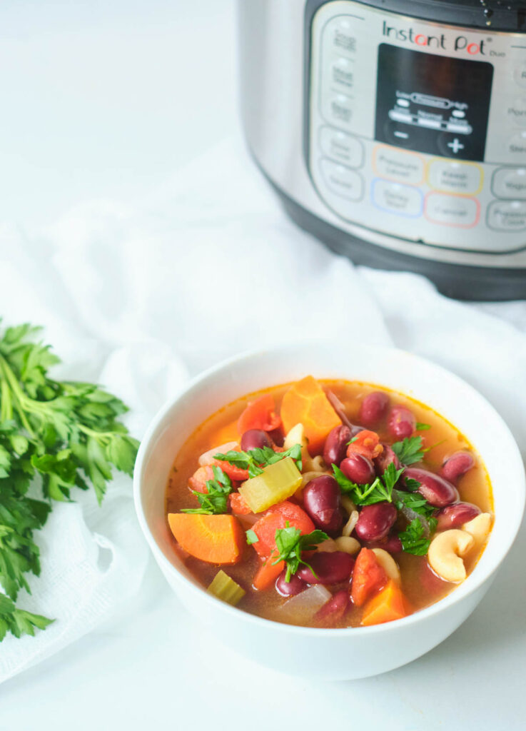minestrone soup in white bowl topped with fresh parsley