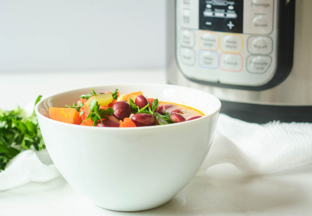 minestrone soup in white bowl with instant pot in the background