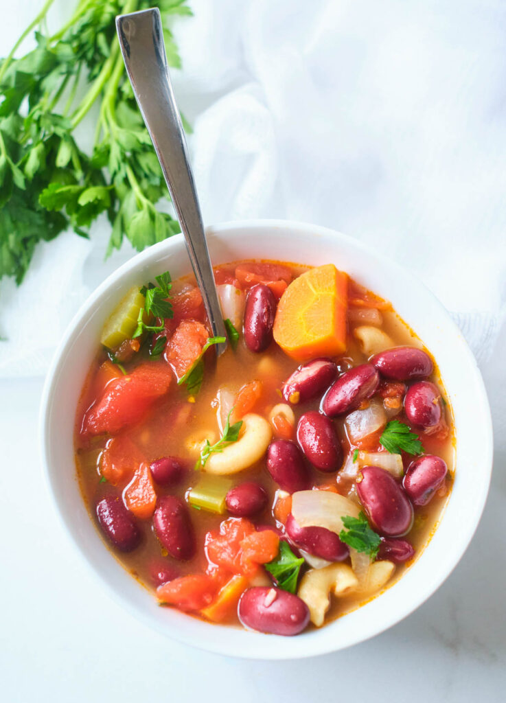 spoon in white bowl of vegetable soup