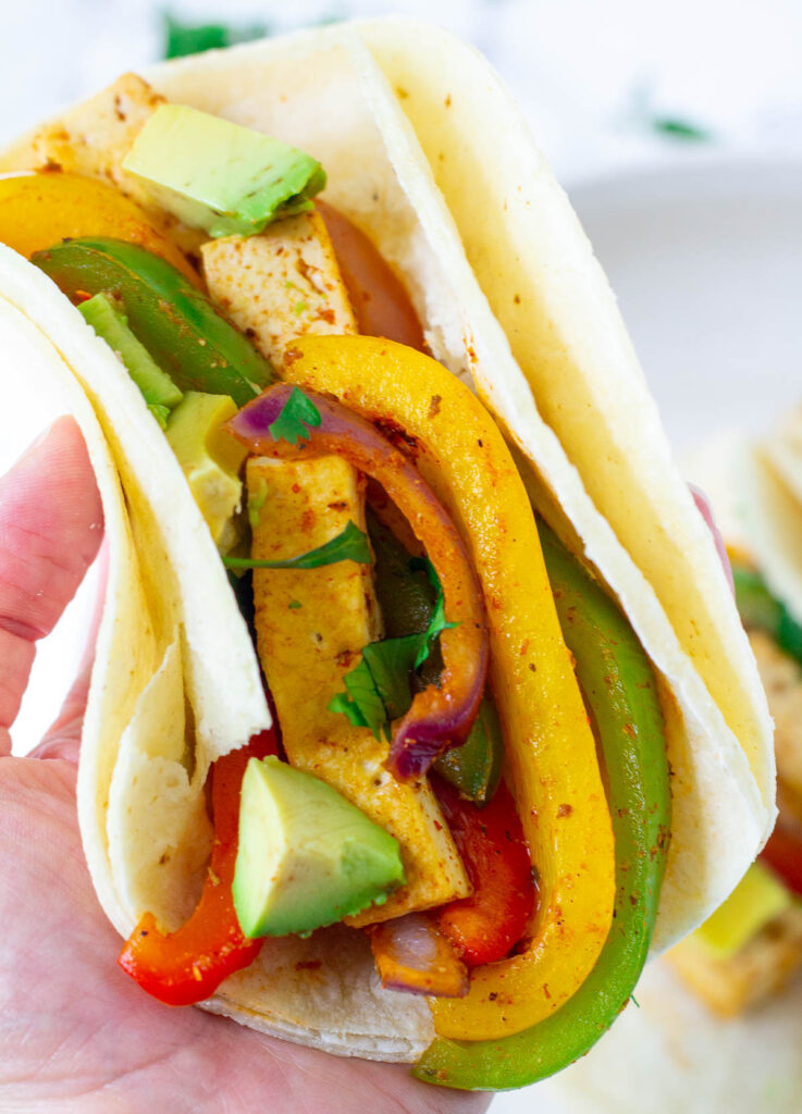 hand holding a fajitas in a corn tortilla with tofu and peppers