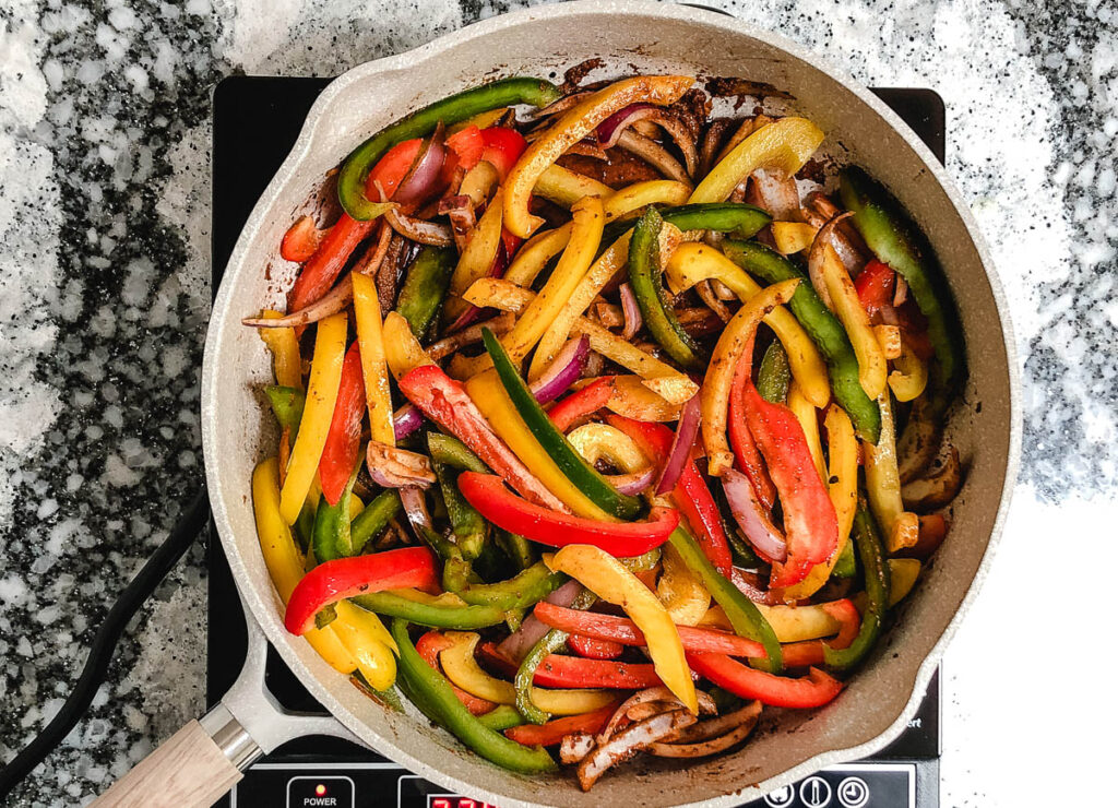 large skillet with seasoned bell pepper slices