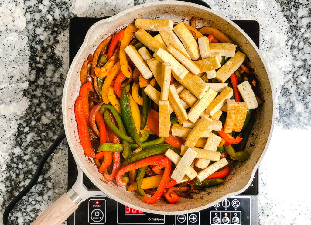 large skillet with bell pepper slices on one side, and crispy tofu strips on the other