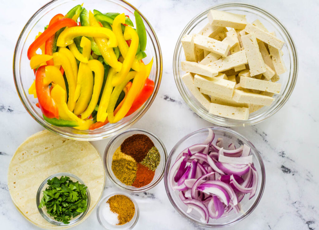 bell pepper slices, tofu strips, red onion slices, spices, corn tortillas and chopped cilantro