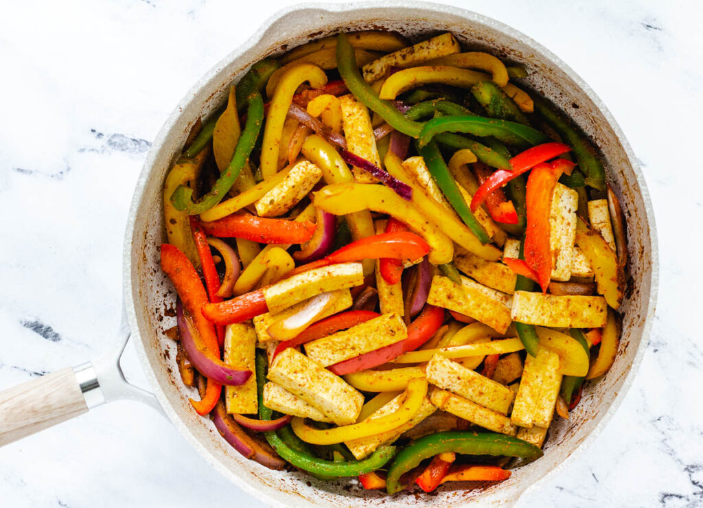 large skillet filled with tofu chunks and peppers with seasoning