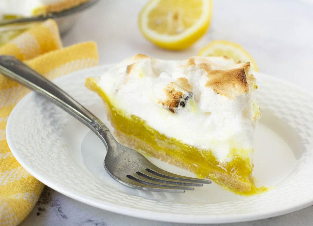 slice of vegan lemon meringue pie on white plate with fork