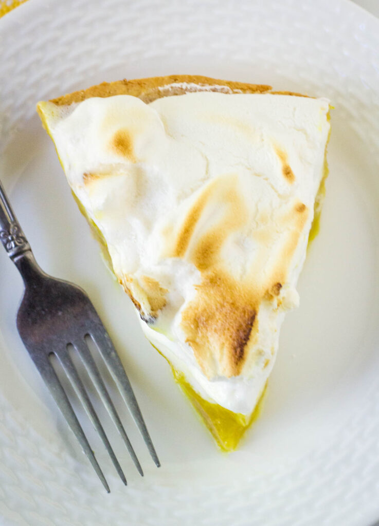 overhead shot of slice of meringue pie on white plate with fork
