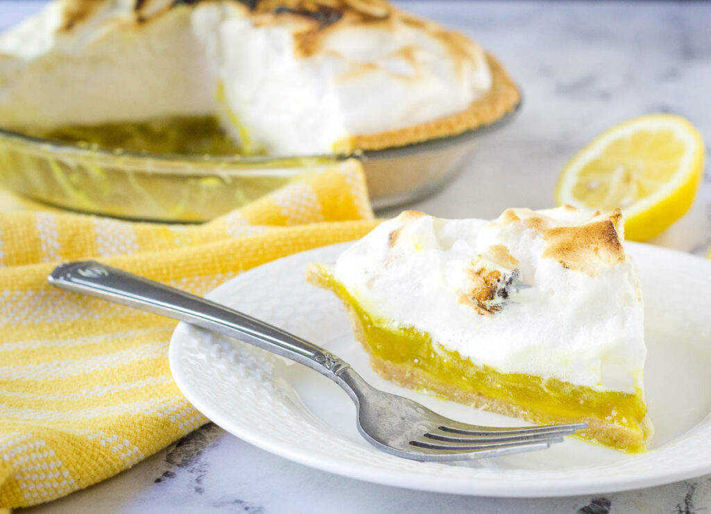 vegan lemon meringue pie on white plate with fork with pie in background