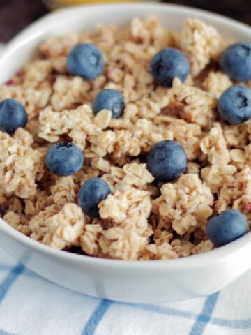 bowl of granola topped blueberries
