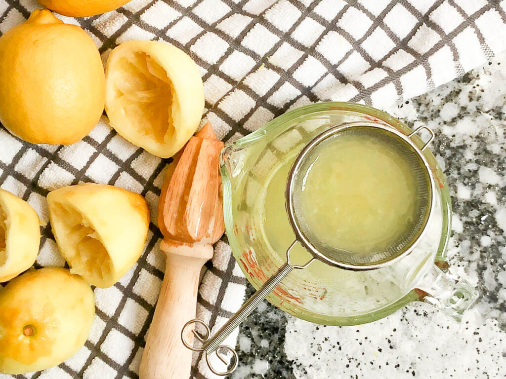 lemon juice in strainer over glass measuring cup